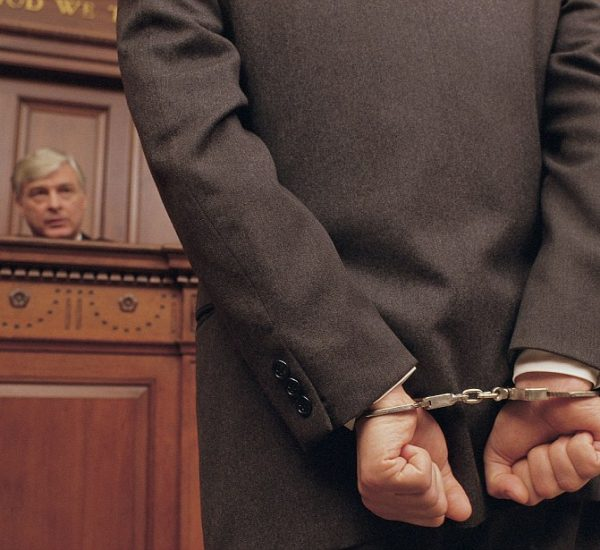 Businessman in court with handcuffs on